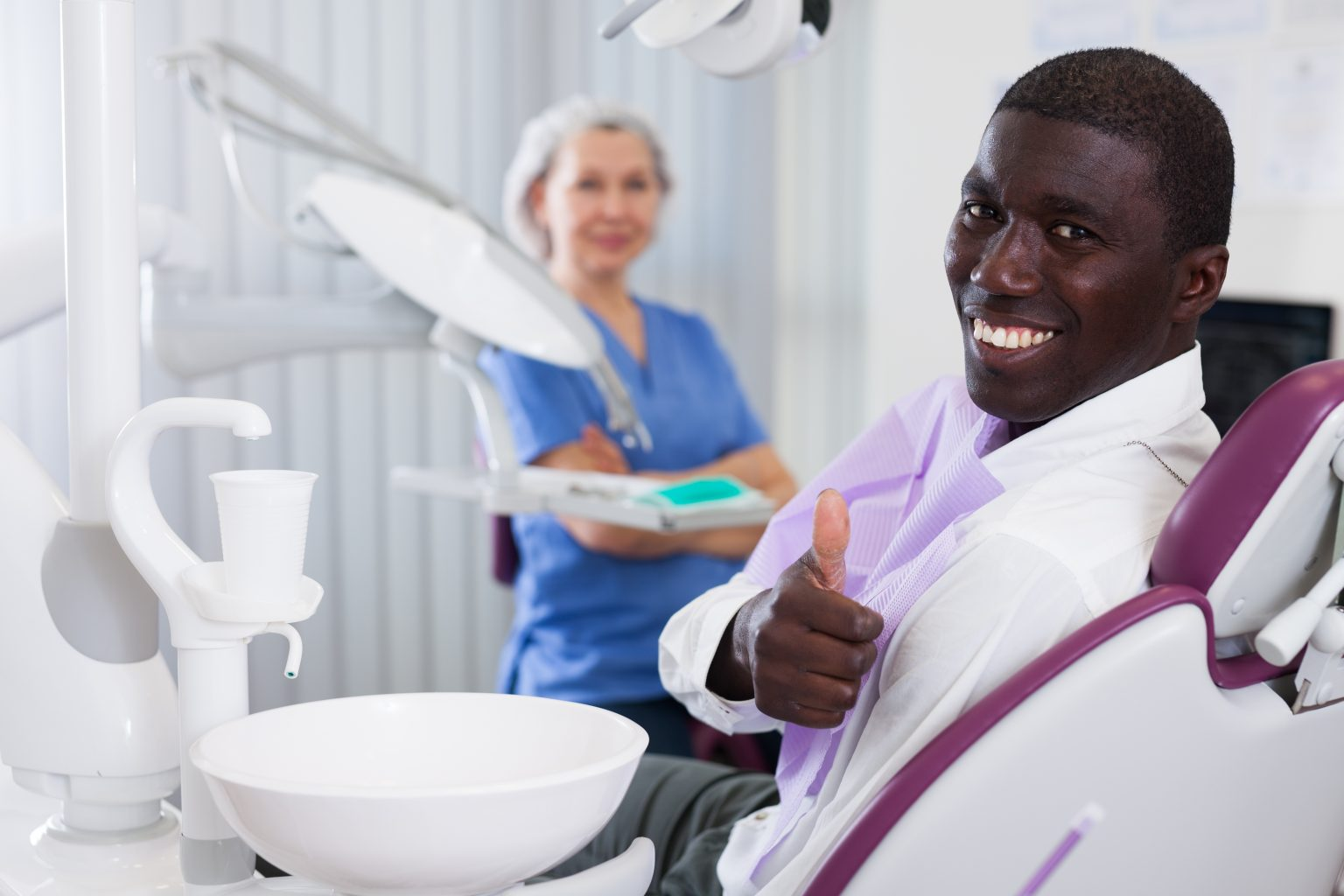 Happy African American Man Sitting In Dental Chair After Teeth Cure Giving Thumb Up